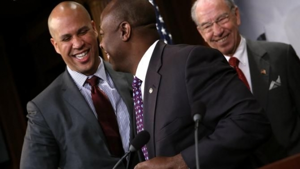 Sen. Cory Booker (D-N.J.) greets Sen. Tim Scott (R-S.C.) as Senate Judiciary Committee Chairman Sen. Chuck Grassley (R-Iowa) looks on during a press conference Oct. 1, 2015, at the U.S. Capitol announcing a bipartisan effort to reform the criminal-justice system.