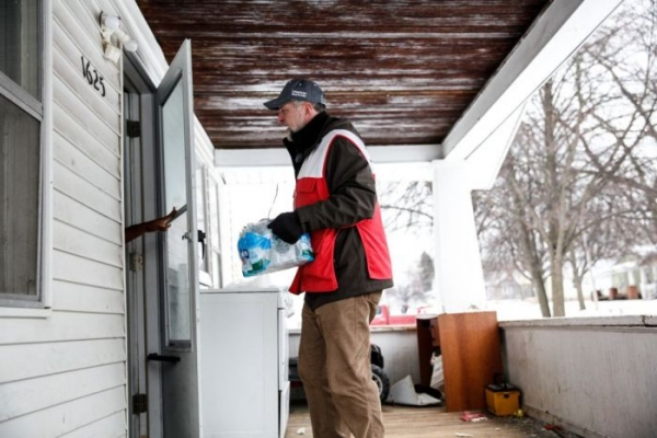 A volunteer goes door to door with bottled water.