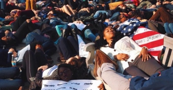 "Hundreds of university and high school students staged a ""die-in"" in Harvard Square, Massachusetts in memory of slain black teenager Michael Brown."