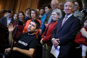 Ady Barkan speaks at a Dec. 19, 2017, press conference against the GOP tax bill organized by congressional Democratic leaders, including House Minority Leader Nancy Pelosi (D-Calif.)